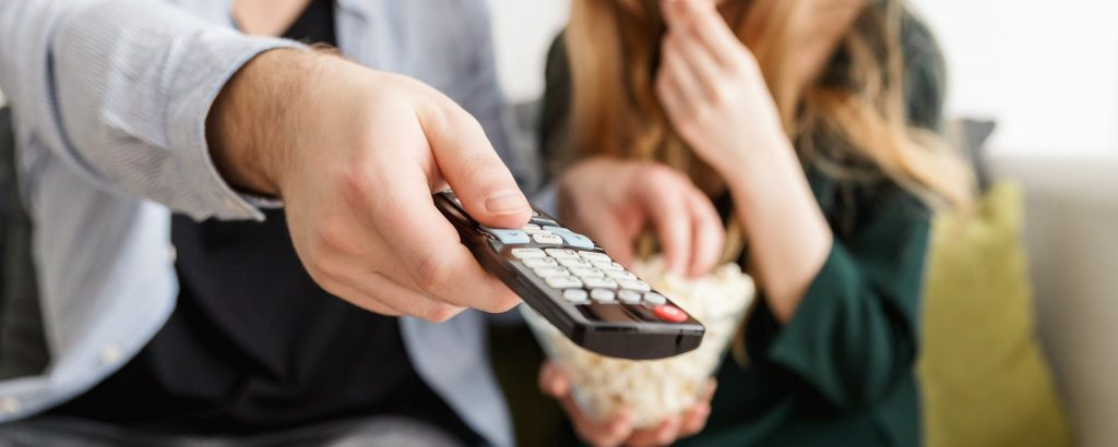 Two people sit on a sofa. One holds a TV remote in their outstretched hand. The other has a bowl of popcorn on their lap.