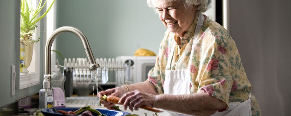 Elderly woman washing vegetables